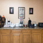 breakfast area with coffees, waffle maker, microwave, and cutlery at Super 8 by Wyndham Fort Worth South