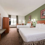 guest room with two beds, table with chairs, TV, and nighstand at Super 8 by Wyndham Fort Worth South
